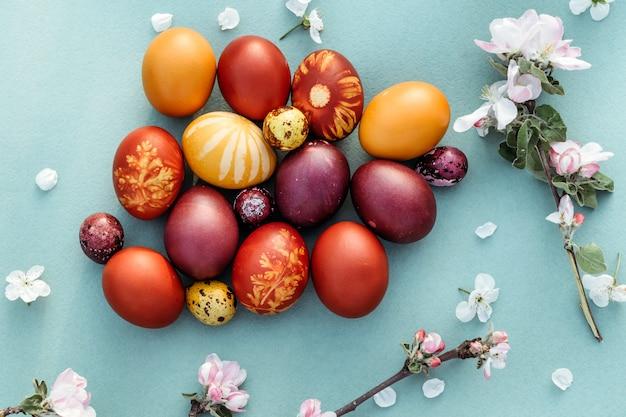 Fundo de páscoa, ovos de galinha e codorna multi-coloridas sobre fundo azul brilhante fundo de páscoa com flores da primavera.