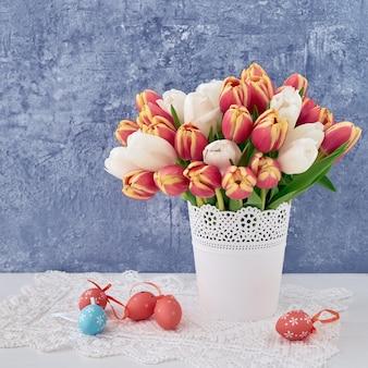 Fundo de páscoa. ovos de páscoa decorativos e tulipas vermelhas em um vaso. copie o espaço. celebração da páscoa