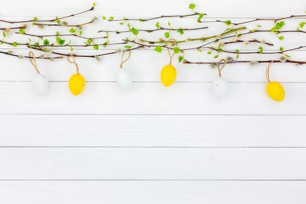 Fundo de páscoa. ovos de páscoa, galho de árvore de salgueiro, galhos de bétula em fundo branco de madeira. cópia de