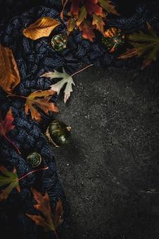 Fundo de pedra escura com outono vermelho e amarelo folhas camisola quente ou cobertor e pequenas abóboras, vista superior cópia espaço