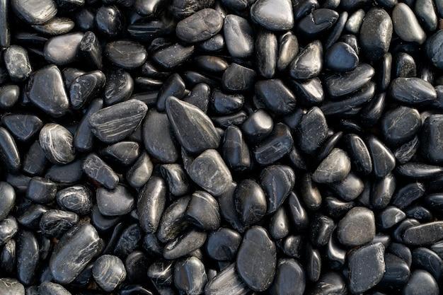 Fundo de pedras de praia preto liso brilhante.