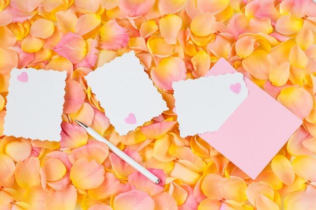 Fundo de pétalas de rosa cor de rosa, envelope rosa, corações, caneta e folhas de papel