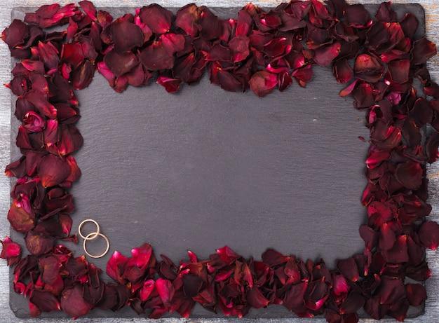 Fundo de pétalas de rosa vermelhas e alianças de casamento.