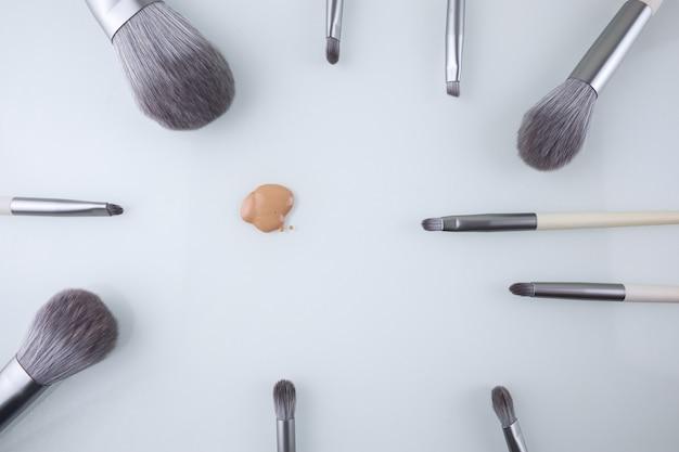 Fundo de pincéis de maquiagem e uma gota de base para o rosto