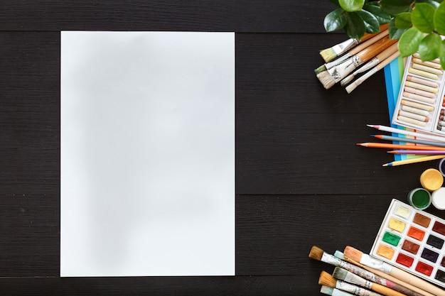Fundo de pintura criativa fornece pincéis de papel paintbox na mesa de madeira preta
