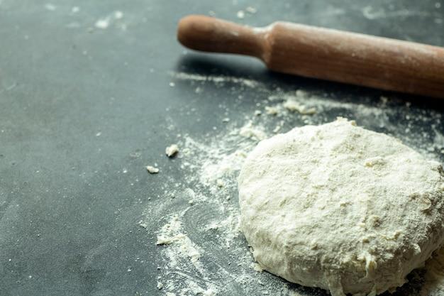 Fundo de pizza de massa. cozinhar massa de pizza ou pão na mesa da cozinha. fundo de alimentos