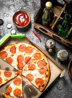Fundo de pizza. pepperoni com cerveja. sobre um fundo rústico.