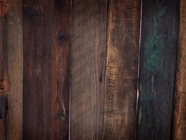 Fundo de placas naturais pintadas com textura de madeira marrom e verde escuro.