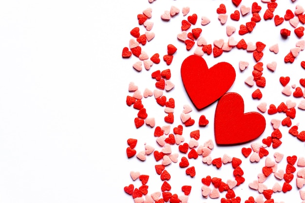 Fundo de polvilha, corações vermelhos polvilhe açúcar, decoração para bolo e padaria. vista superior, configuração plana. cartão do feriado do dia dos namorados.