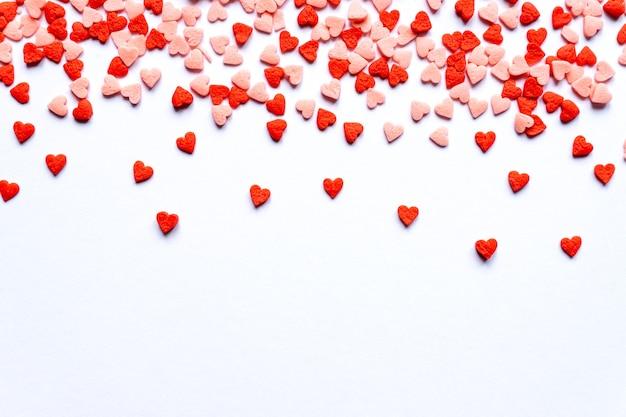 Fundo de polvilha, corações vermelhos polvilhe açúcar, decoração para bolo e padaria. vista superior, configuração plana. feriado do dia dos namorados.