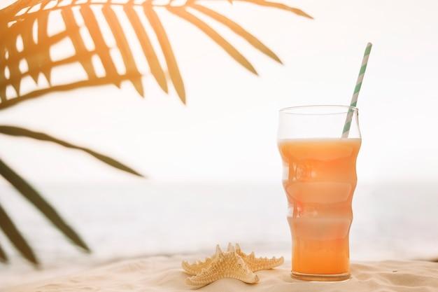 Fundo de praia com cocktail e folha de palmeira
