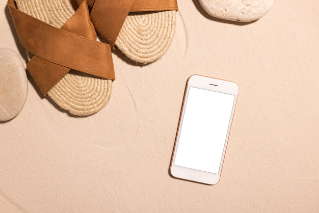 Fundo de praia com sandálias marrons de telefone celular e pedra em uma praia de areia no conceito de sol summe ...
