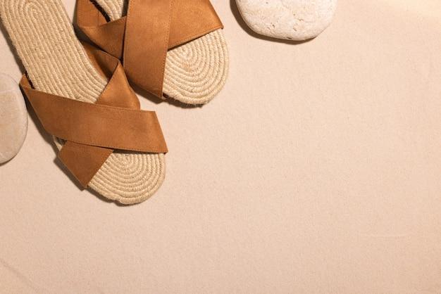 Fundo de praia com sandálias marrons e pedra em uma praia de areia nas férias de verão do conceito de sol em ...