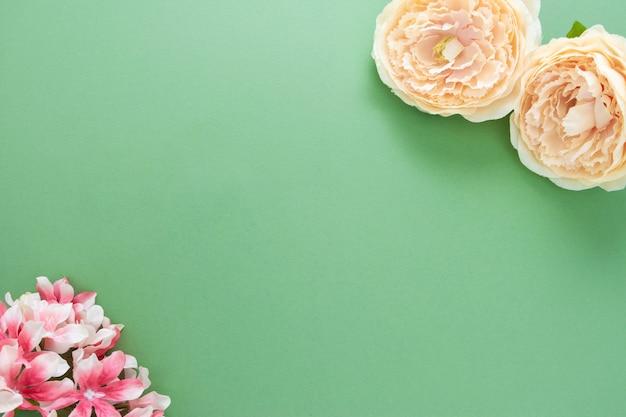 Fundo de primavera com composição de flores na placa verde. moldura festiva ou borda. vista superior com espaço de cópia.