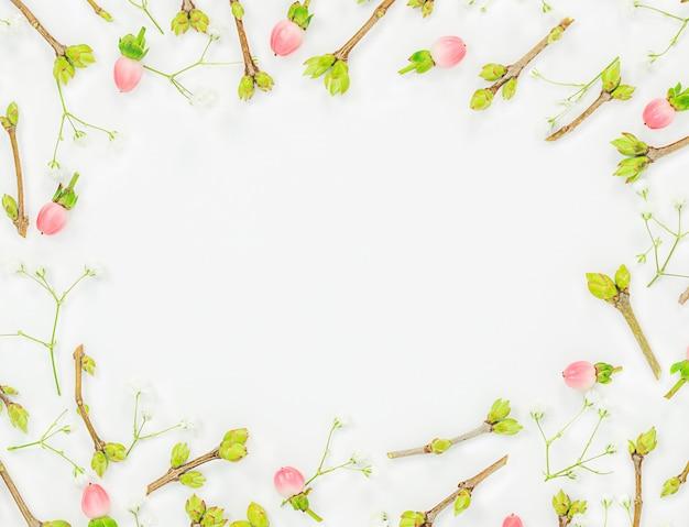 Fundo de primavera de pequenos galhos com botões e bagas cor de rosa em um fundo claro com um círculo em branco no meio