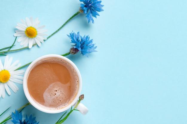 Fundo de primavera. flores, camomila e uma xícara de café quente. vista do topo. copie o espaço