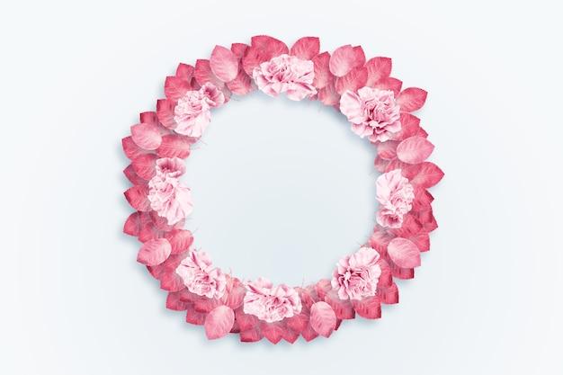 Fundo de primavera, frame redondo, uma coroa de cravos rosa e vermelhos sobre um fundo claro