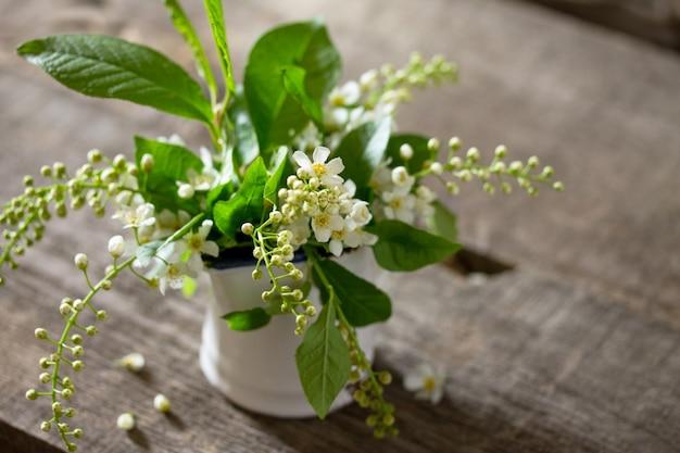 Fundo de primavera. lindas flores brancas frescas de cereja de pássaro em fundo de madeira.