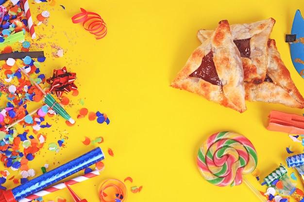 Fundo de purim com fantasia de festa e biscoitos hamantaschen.