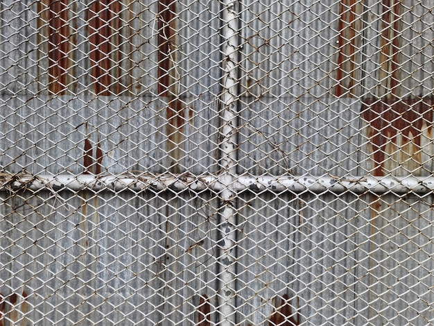 Fundo de quadro completo de parede de malha de arame contra folhas de zinco corrugadas enferrujadas
