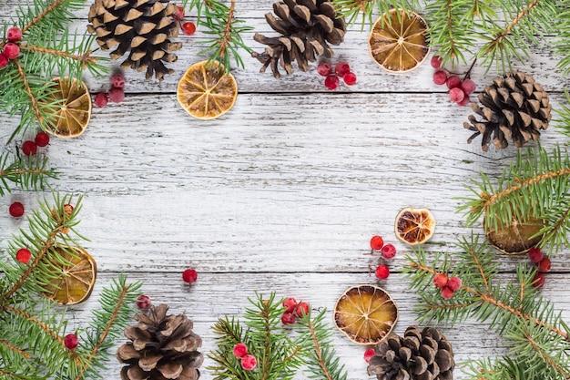 Fundo de quadro de galhos de natal com bagas de viburno cones e fatia de limão seco