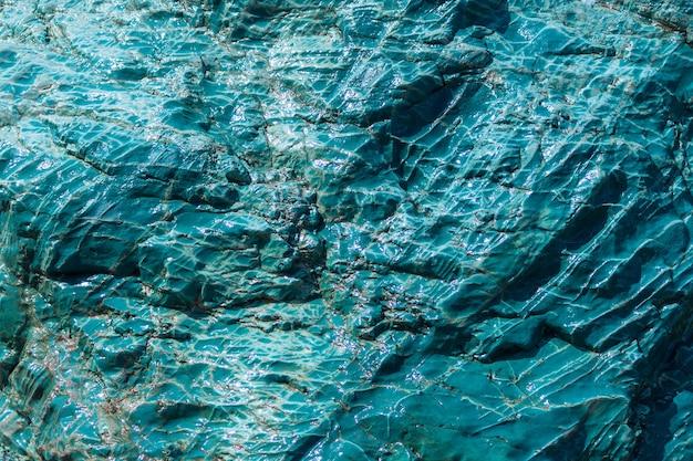 Fundo de rocha verde azulado. superfície da montanha rachada turquesa. fundo de pedra, copie o espaço.