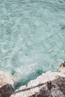 Fundo de rochas e águas da costa do mar