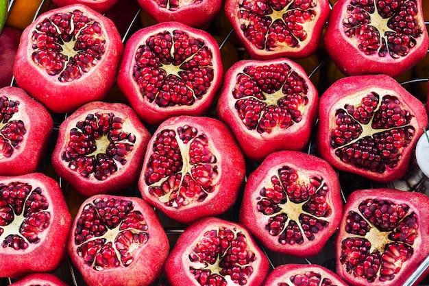 Fundo de romã maduras frescas com incisão no balcão no mercado de rua.