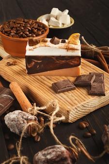 Fundo de sobremesa saborosa. pedaço de bolo, barras de chocolate, açúcar refinado, grãos de café, canela e caqui seco na mesa de madeira rústica, vista lateral. publicidade de design