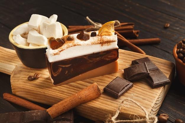 Fundo de sobremesa saborosa. pedaço de bolo, barras de chocolate, açúcar refinado, grãos de café e canela na mesa de madeira rústica, vista lateral. publicidade de design