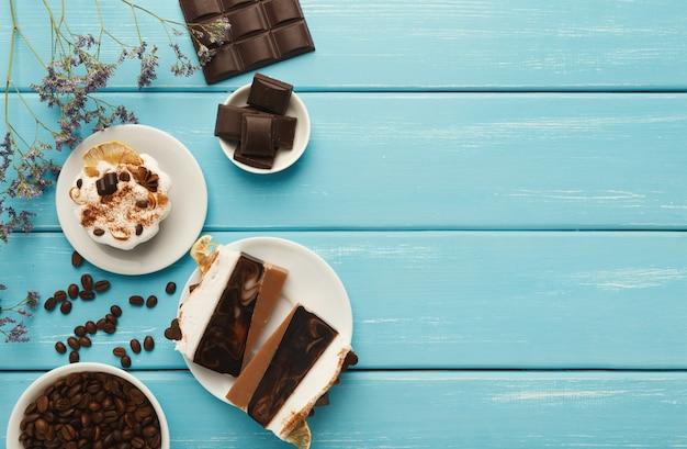 Fundo de sobremesas saborosas. vários bolos e barras de chocolate na mesa rústica azul com grãos de café espalhados e flores violetas, estilo provençal, vista de cima, cópia espaço
