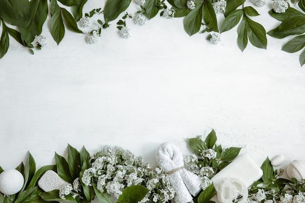 Fundo de spa com acessórios de banho, produtos de saúde e beleza com flores frescas.