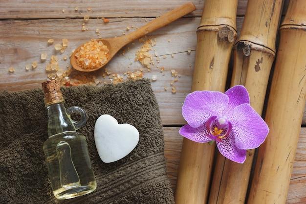 Fundo de spa com bambu, flor de orquídea, toalha e pedra em forma de coração