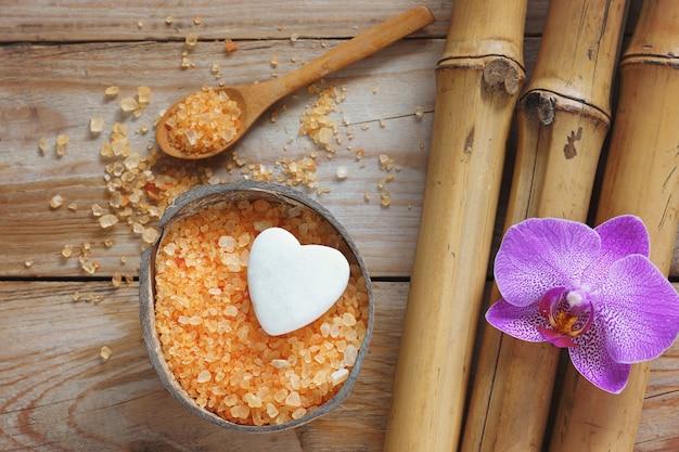 Fundo de spa com bambu, sal de banho, flor de orquídea e pedra em forma de coração
