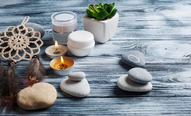 Fundo de spa com frascos de cosméticos, pedras e velas acesas