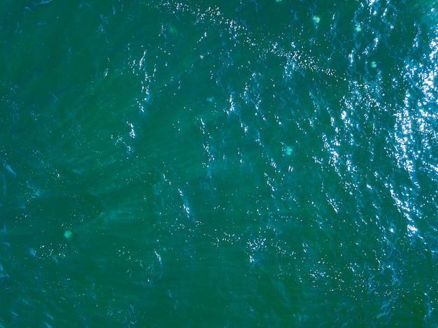 Fundo de superfície da água de vista superior aérea. foto da superfície do mar de olho de pássaro do drone. oceano azul de cima. fundo natural mínimo. Foto Premium