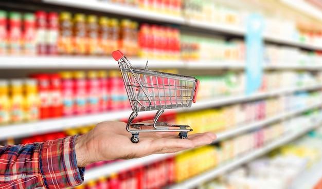 Fundo de supermercado de supermercado com carrinho na mão, comida e mantimentos borrados nas prateleiras das lojas