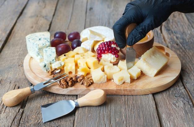 Fundo de tábua de queijos. a mão do chef em uma luva pica o queijo com uma faca especial.