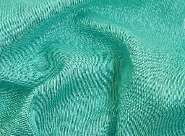 Fundo de tecido amarrotado de cor esmeralda, textura de tecido leve e arejado, transparente.
