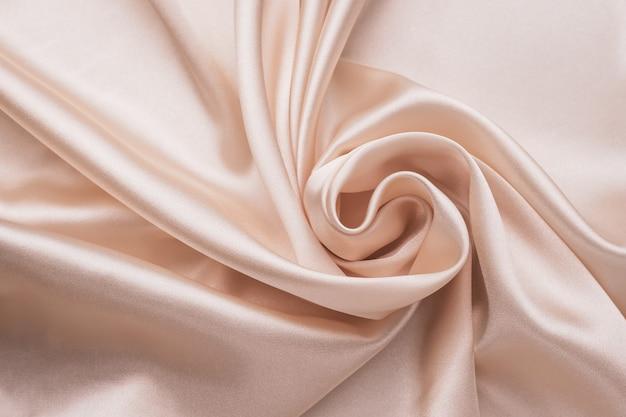 Fundo de tecido de seda enrugada elegante suave. resumo a textura cetim amassado. cor creme. material pastel ondulado macio, têxtil brilhante rosa. pano dobrado, papel de parede.