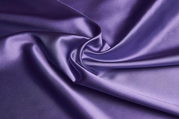 Fundo de tecido de seda roxo, close-up. a textura de tecido de cetim violeta suave pode ser usada como plano de fundo abstrato com espaço de cópia