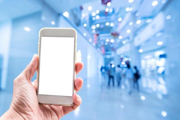 Fundo de tecnologia, mão segurando o celular com tela vazia e shopping turva