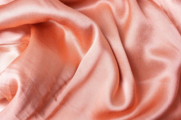 Fundo de tela de cetim rosa pêssego. estilo flat lay