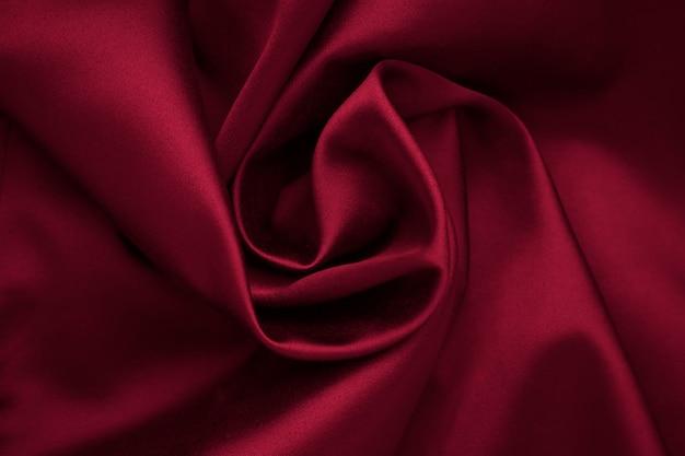 Fundo de tela vermelho romântico. dobras de seda, cetim escuro, vincos têxteis, padrão natural, textura brilhante de pano.