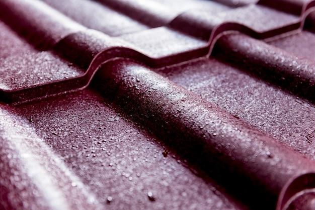 Fundo de telhas de telhado metálico vermelho com gotas de água.