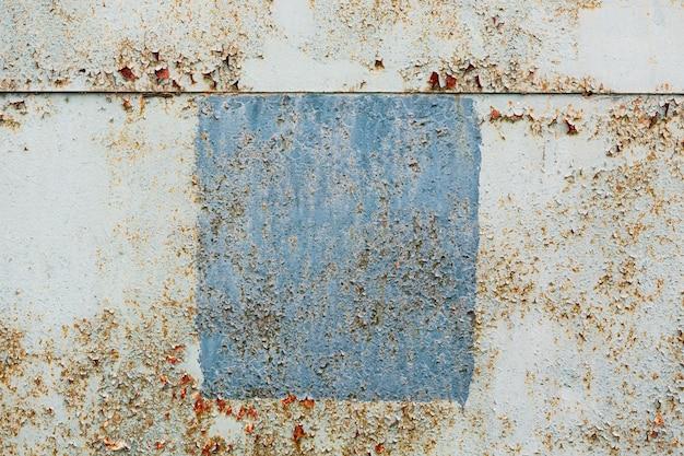 Fundo de textura áspera ao ar livre com um quadrado azul de tinta