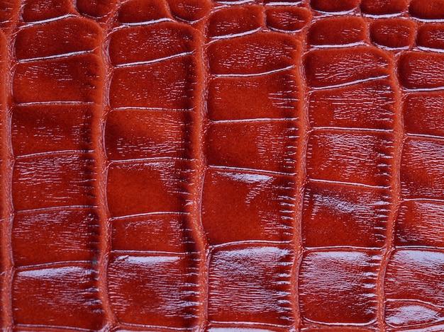 Fundo de textura de couro de pele de crocodilo vermelho genuíno. foto macro