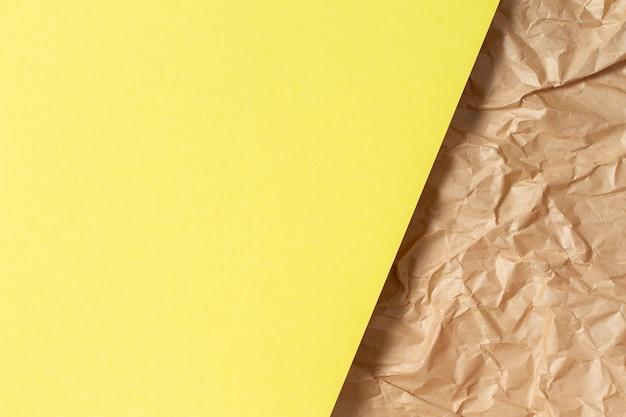 Fundo de textura de papel geométrico abstrato. folha de papel em branco de cor amarela sobre fundo reciclado de papel pardo amassado