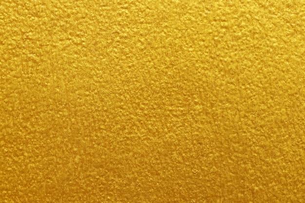 Fundo de textura de parede de concreto de cimento dourado com estuque áspero e velho grunge.