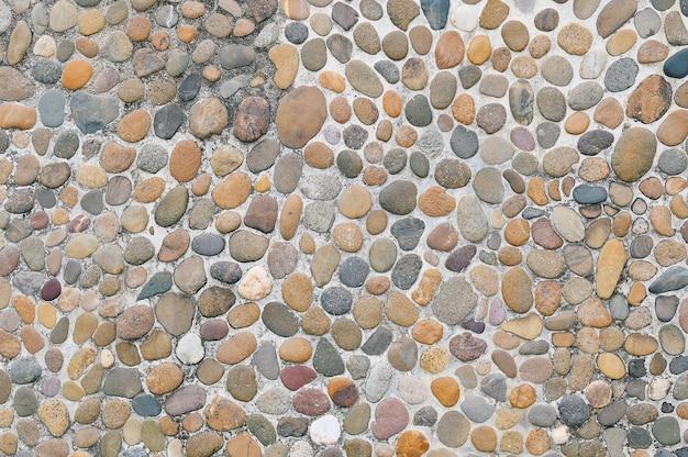 Fundo de textura de parede de pedra de cascalho pequenas pedras que foram erodidas pela água são usadas para decorar a parede.